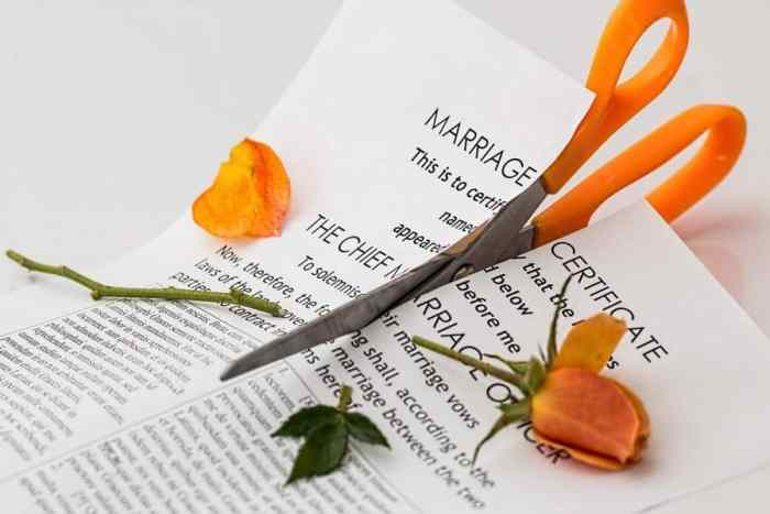 scissors cutting through marriage certificate after divorce
