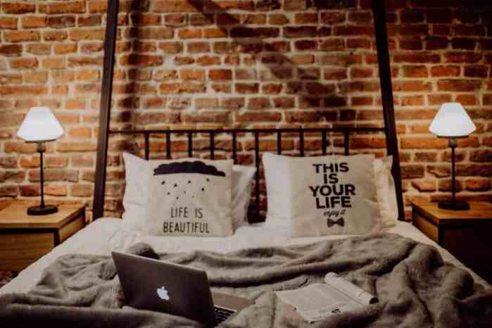 Bed with brick background and mac laptop on bed