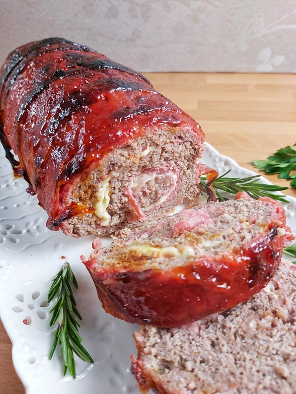 The best low carb and ketoBest Keto Bacon Weapped Cheese Stuffed Meatloaf recipe that it´s tender and juicy on the inside and topped with a zesty topping!