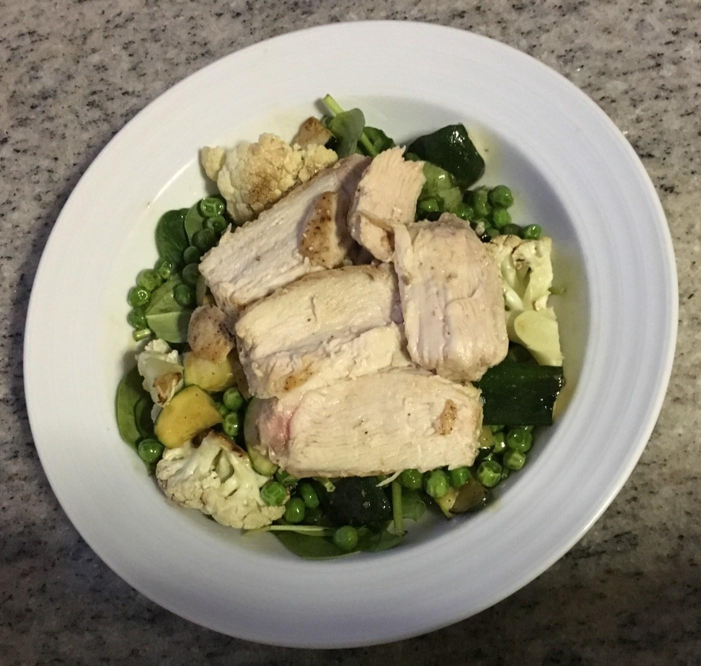 Chicken breast over warm pea, zucchini, cauliflower and spinach salad