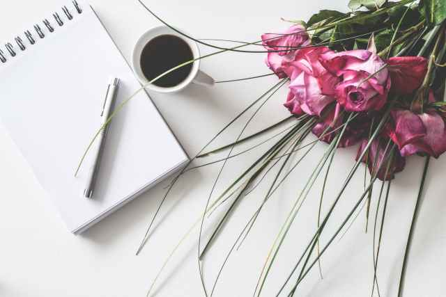 red rose flowers bouquet on white surface beside spring book with click pen and cup of cofffee