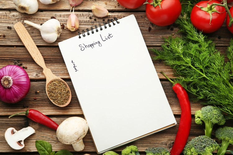 Blank shopping list on paper with vegetables on wooden table