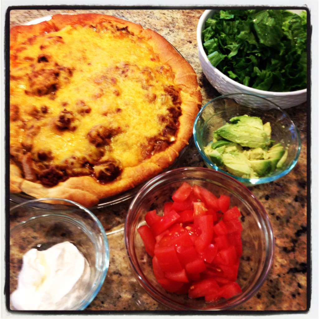 Taco pie covered in melted cheese and veggies on the side.