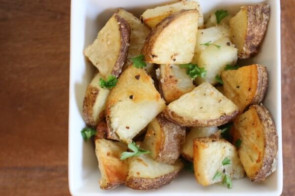 Whole garlic cloves and grated Parmesan cheese make these Garlic Roasted Potatoes a simple side dish the whole family will enjoy!
