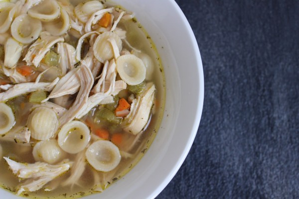 Roasted garlic chicken noodle soup in a white bowl.