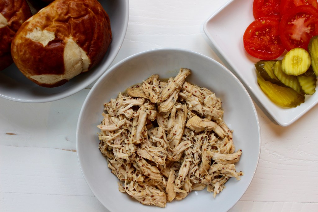 Sweet and tangy slow cooker honey mustard chicken combines simple ingredients for one tasty chicken dish perfect for sandwiches and wraps.