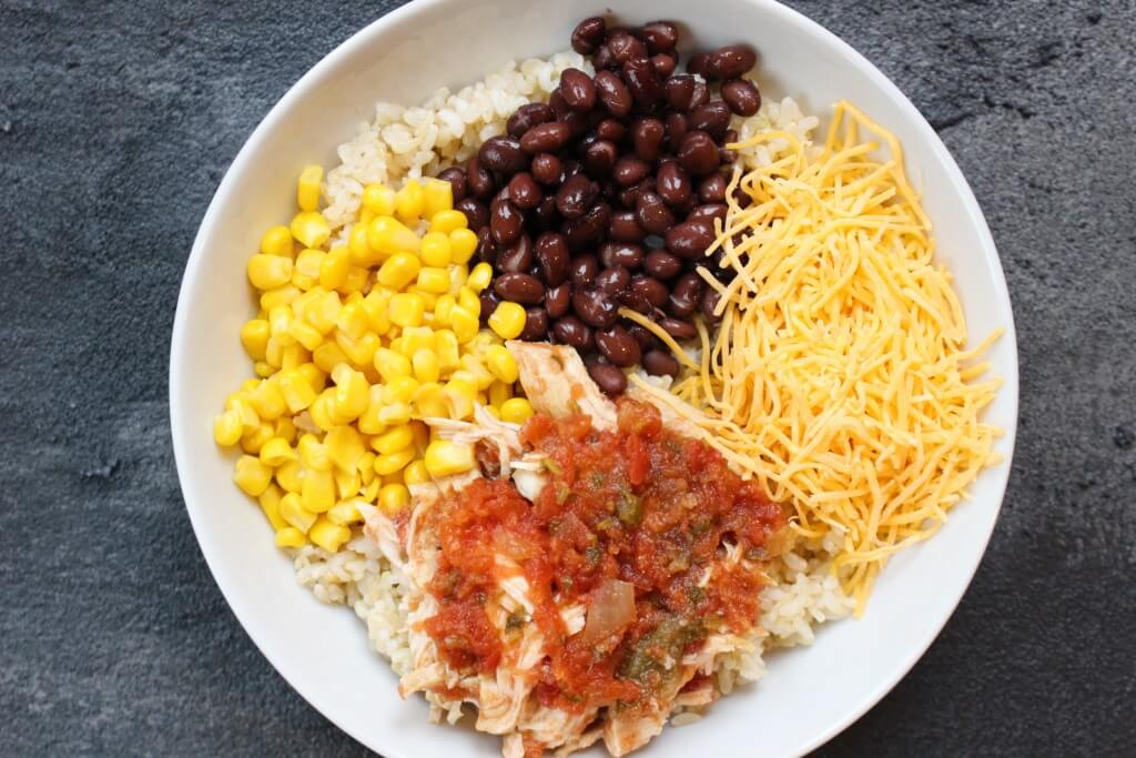Chicken taco bowls are made with fresh taco ingredients and slow cooked chicken, and are served on a bed of brown rice for extra whole grain goodness.