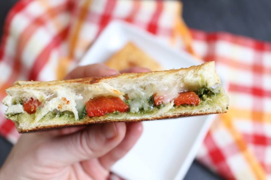 A simple grilled cheese sandwich is packed with extra flavor from pesto and roasted red pepper inside, giving it a gourmet spin!