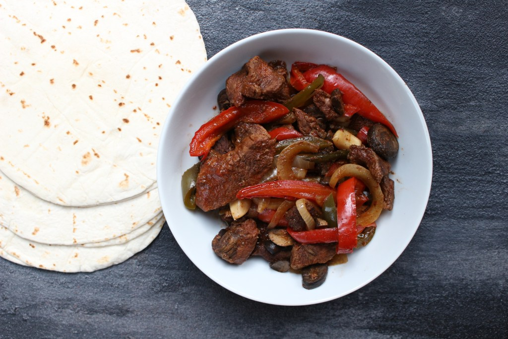 Tender steak and sweet bell peppers come together for one simple weeknight meal with these slow cooker steak fajitas!