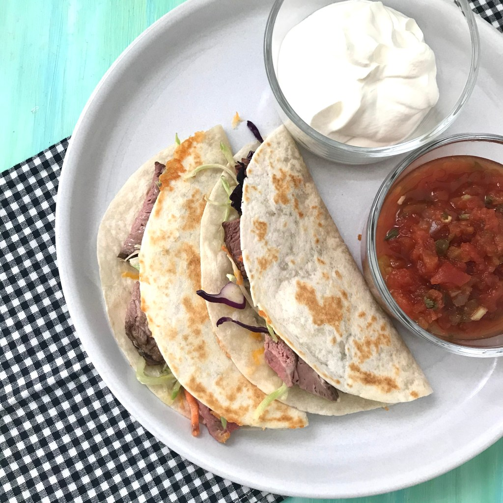 Steak quesadillas on a plate with sour cream and salsa.