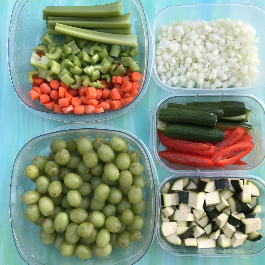 Fruits and veggies chopped, sliced, and diced in clear containers.