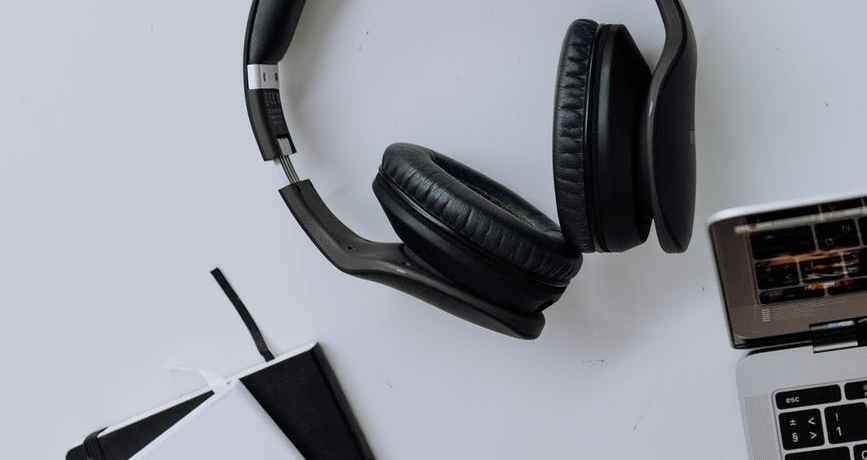 black and silver headphones beside macbook pro