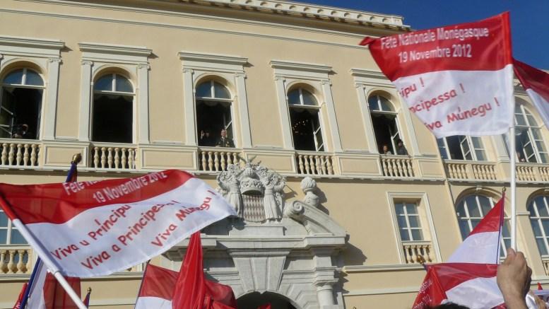 La Popolazione sventola le bandiere in lingua dialettale monegasca durante la Festa Nazionale