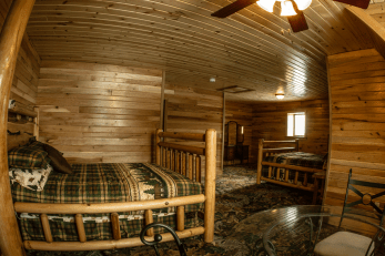 Spacious bedroom with wooden walls, carpeted floor, a table, and two beds