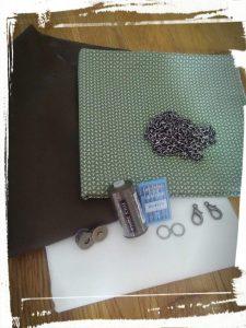 Le matériel pour la réalisation de la pochette en cuir. Peau de cuir, doublure en tissu aimant, chaîne et mousquetons