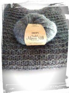 Pull doudou réalisé à partir de laine Drops pliée et avec un pelote en décoration