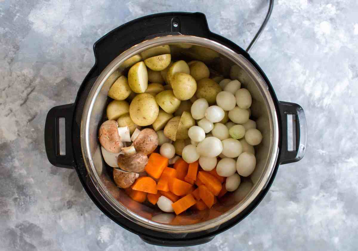instant pot on table filled with potatoes, pearl onions, carrots, and mushrooms