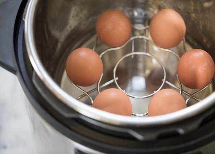 brown eggs in a holder trivet in an instant pot