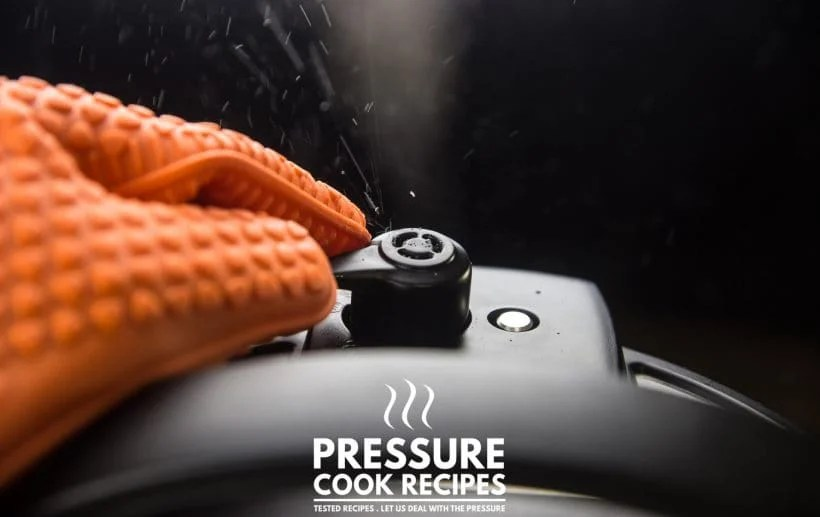 close-up of an instant pot releasing pressure with steam being turned with an orange silicone glvoe
