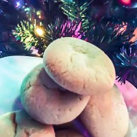 Close-up of sugar cookies on a white plant in front of a lighted christmas tree