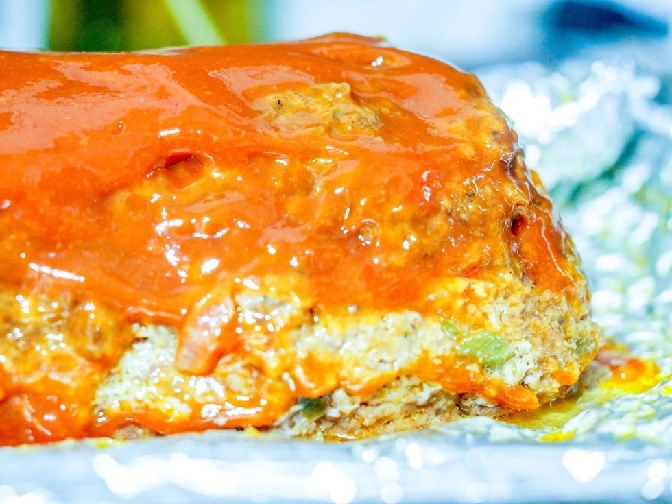 cooked meatloaf with ketchup topping on a baking sheet covered in foil
