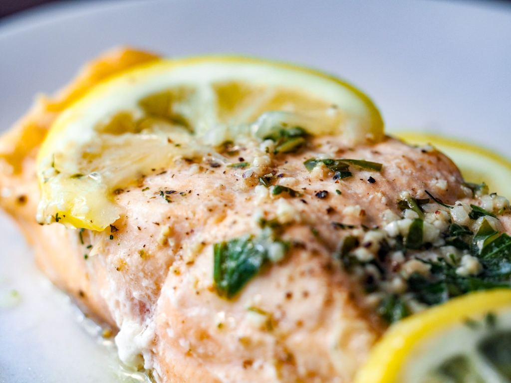 close up of herbed lemon salmon on a white plate with lemon slices