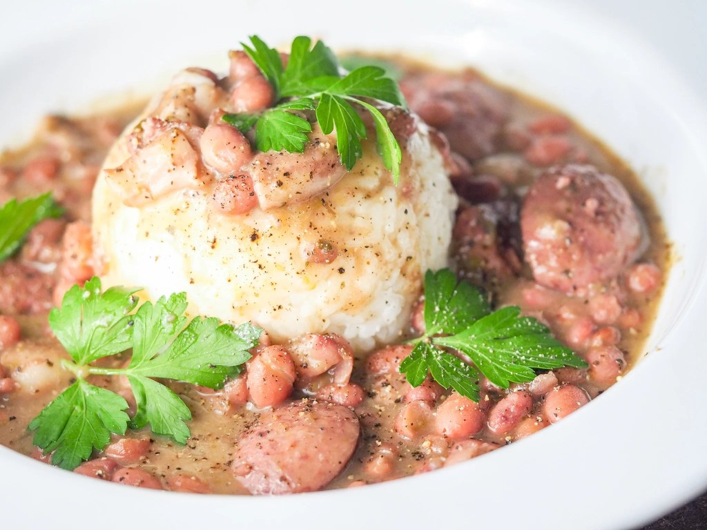 red beans and rice with sausage in a large white bowl with a formed cup of rice in the middle with fresh pepper and parsley garnish