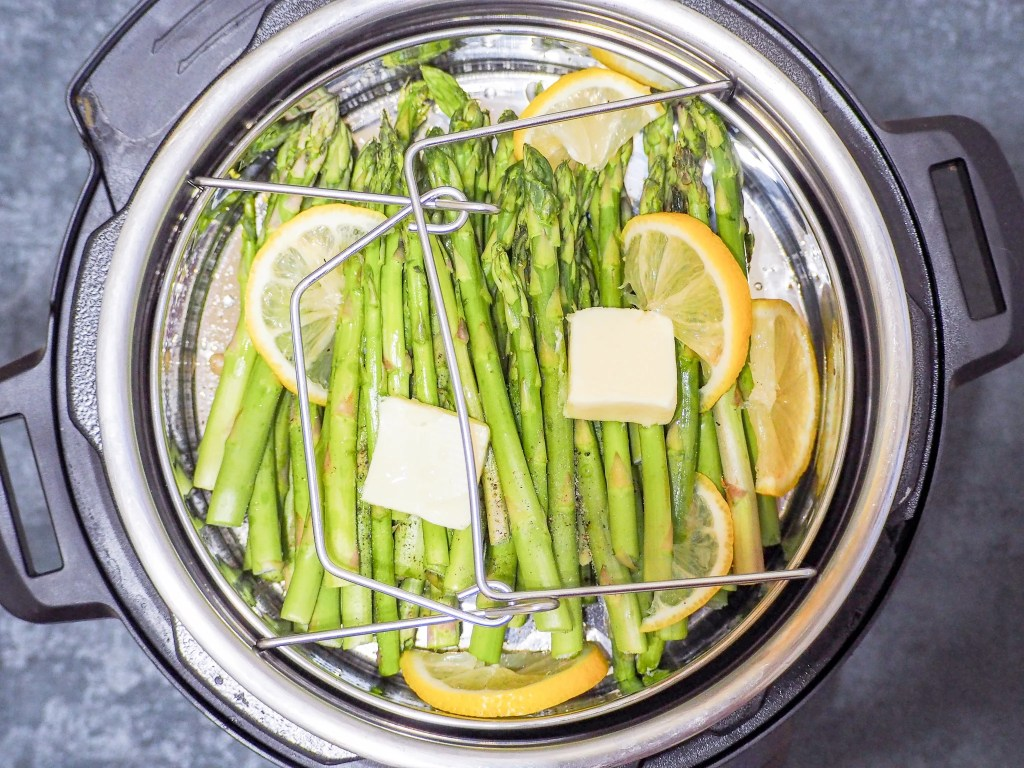 overhead shot of trimmed asparagus in the instant pot with sliced lemons and butter pats