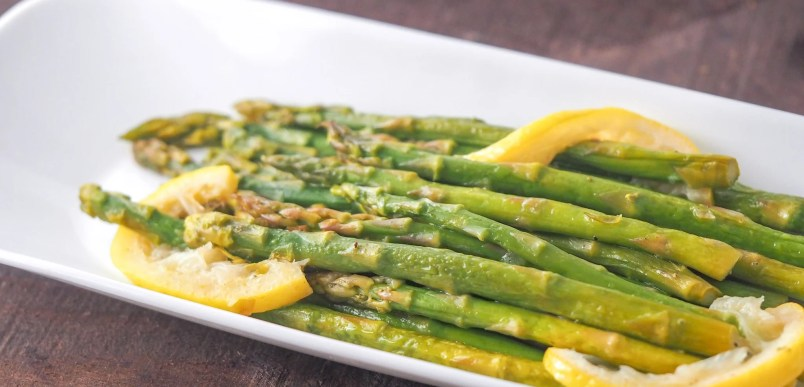 side view of steamed asparagus on plate with lemon slices