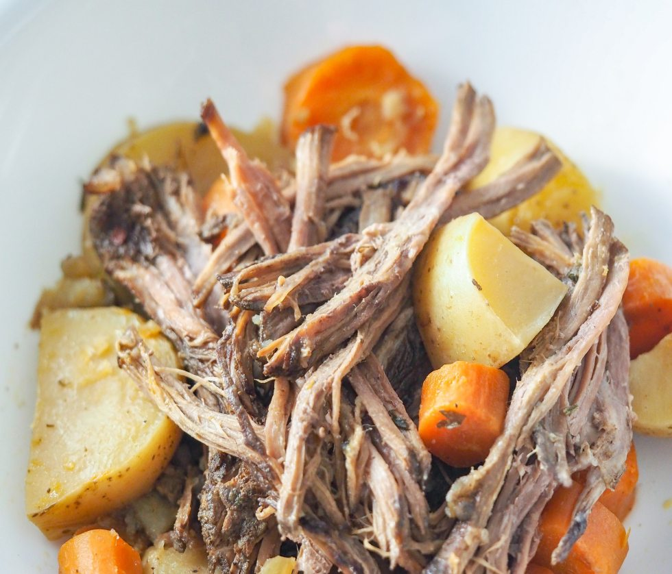 verical view of cooked pot roast in white bowl with potatoes and carrots