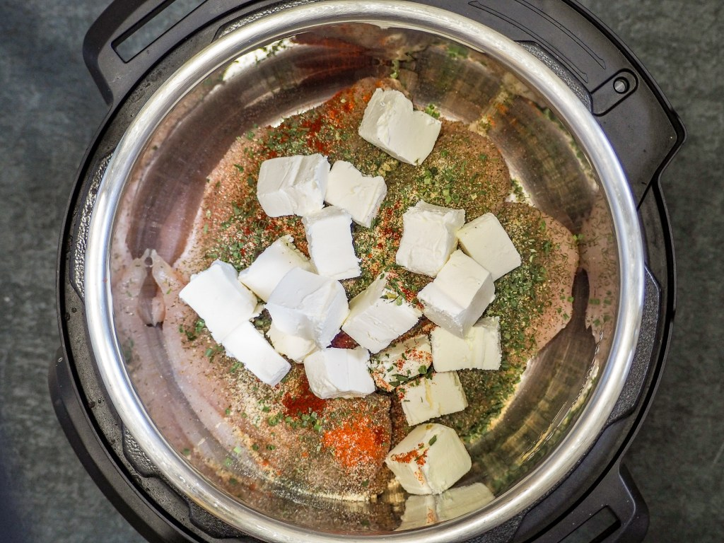 overhead view of chicken breasts in an instant pot in broth topped with spices and cream cheese