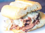 close-up view of french dip sandwich on white plate