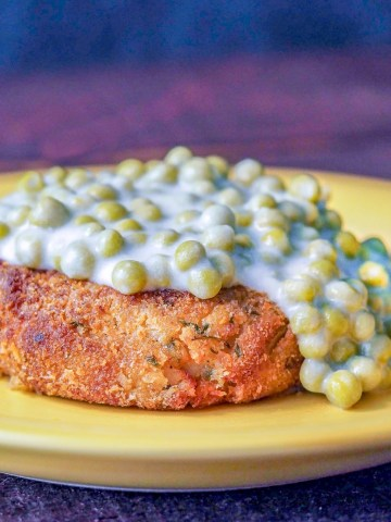 salmon patty on a yellow plate topped with creamed peas