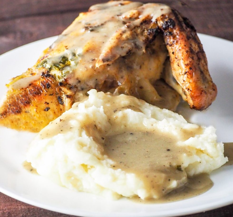 roasted chicken breast with wing attached on a white plate with mashed potatoes and poultry gravy