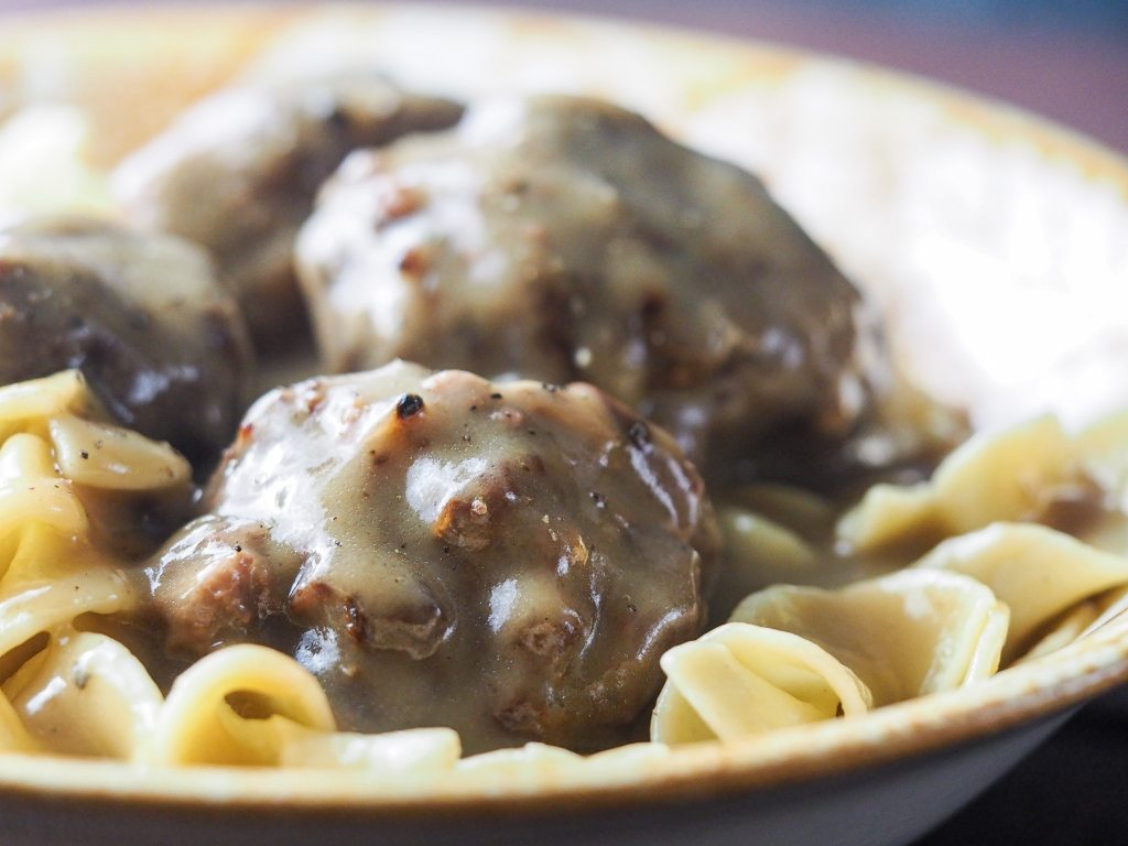 close side view of country meatballs with gravy in bowl with yellow edge