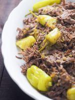 mississippi pot roast on white scalloped edged platter on wooden table