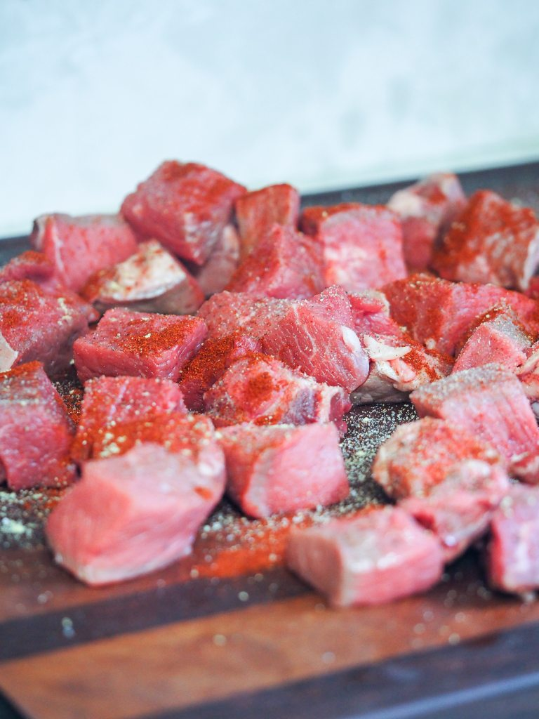 cubed sirloin tip beef on cutting board that has been seasoned