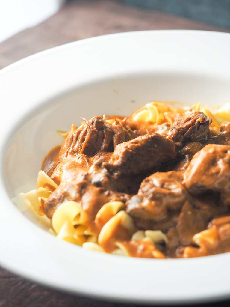 beef stroganoff in large rimmed white bowl over egg noodles