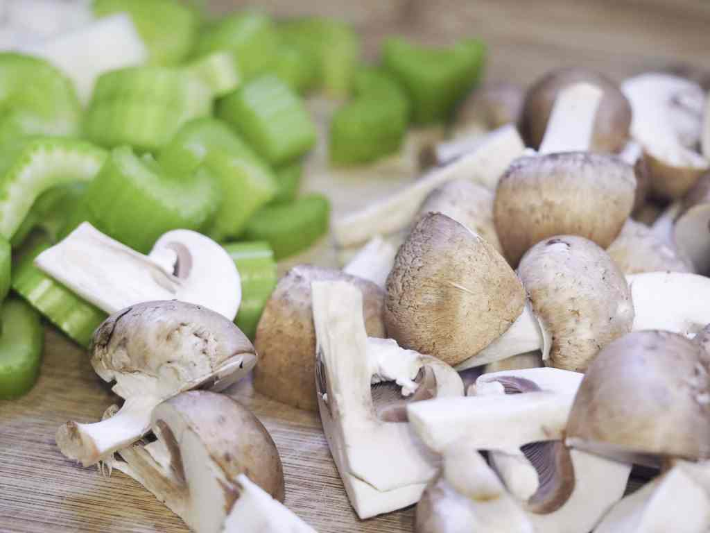 close view of prepped celery, onioins, and mushrooms