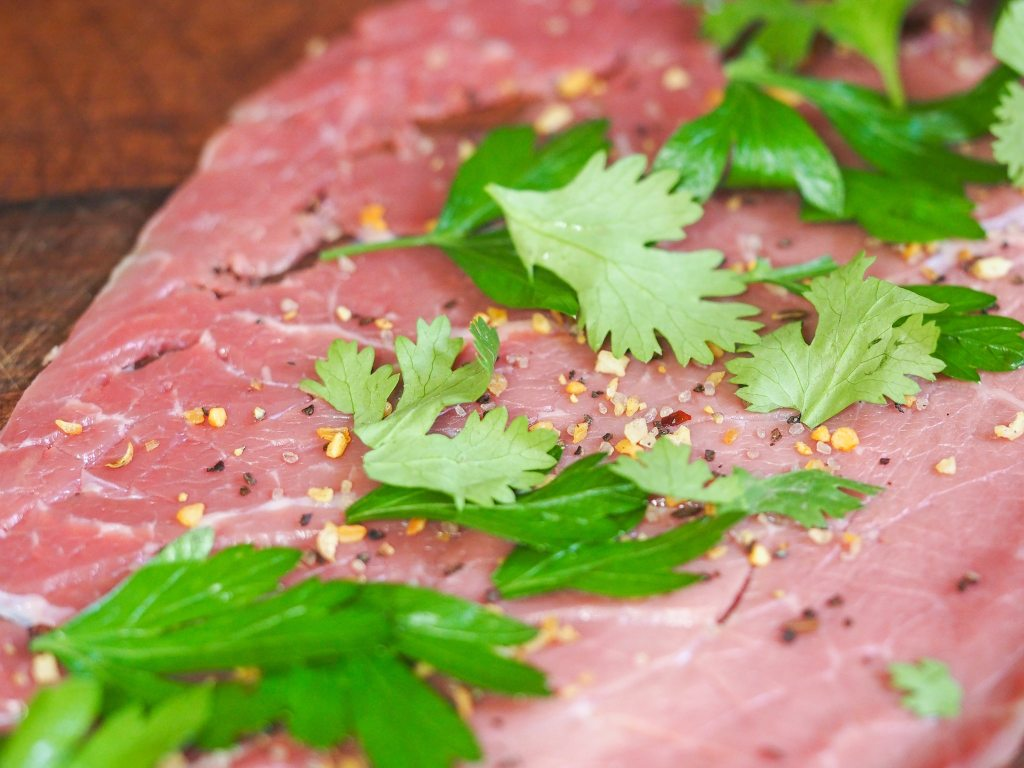 thin cut beef with seasoning and herbs laying flat on a wooden cutting board