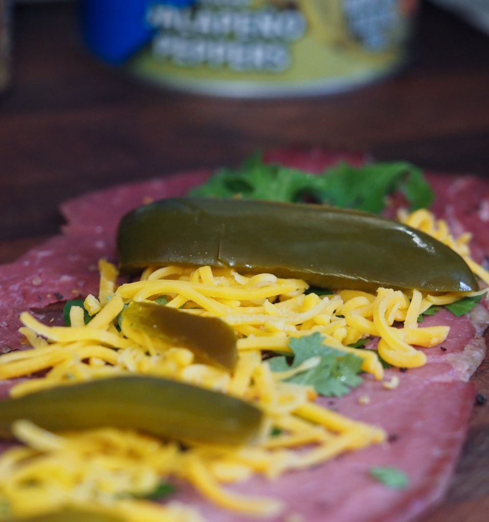 seasoned thin cut beef with herbs, cheddar cheese, and sliced pickled jalapenos on a wooden cutting board