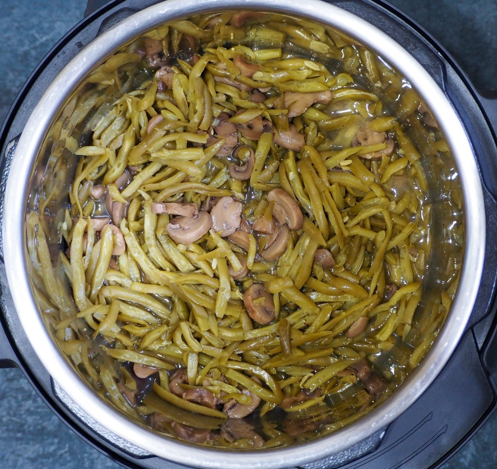 overhead view of canned green beans and mushrooms with chicken broth in the instant pot