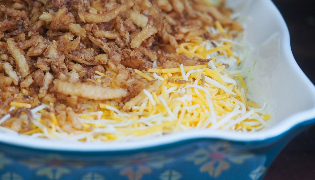 green bean casserole in baking dish topped with cheese and fried onions