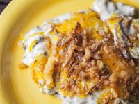 close up view of green bean casserole with cheese on yellow plate