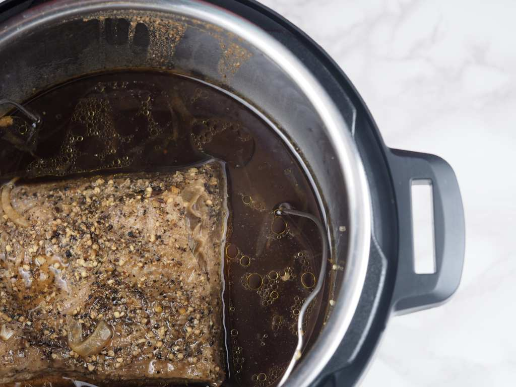 overhead view of cooked brisket in the pressure cooker on a marble tabletop