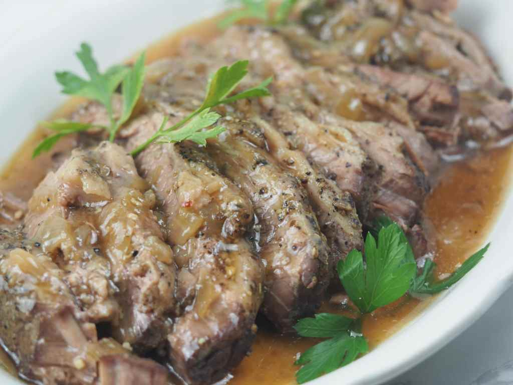 close side view of sliced brisket on white platter with gravy and parsley