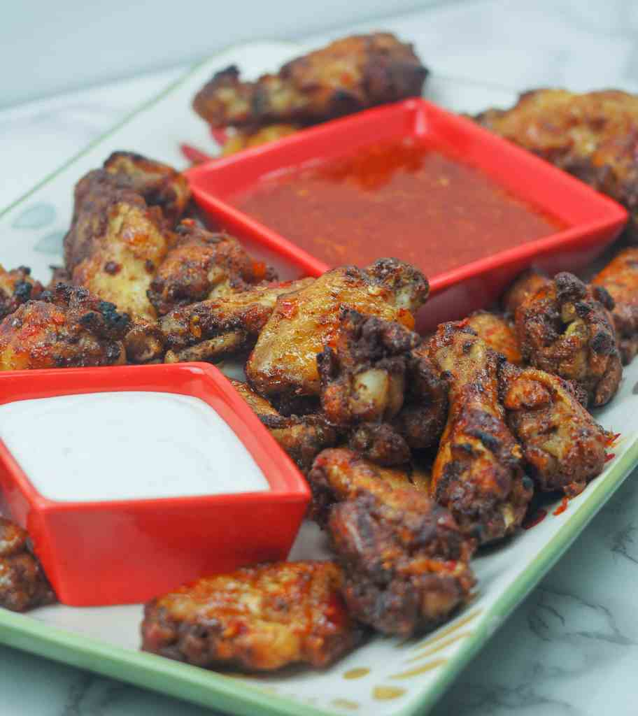 vertical side view of chicken wings on flowered platter with blue cheese and sweet chili dipping sauces in red dishes