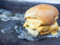 double cheeseburger topped with melted butter on baking sheet