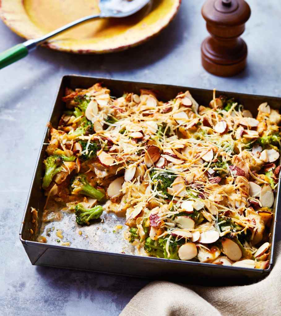 broccoli chicken bake in small metal baking pan with pepper grinder in background with yellow plate
