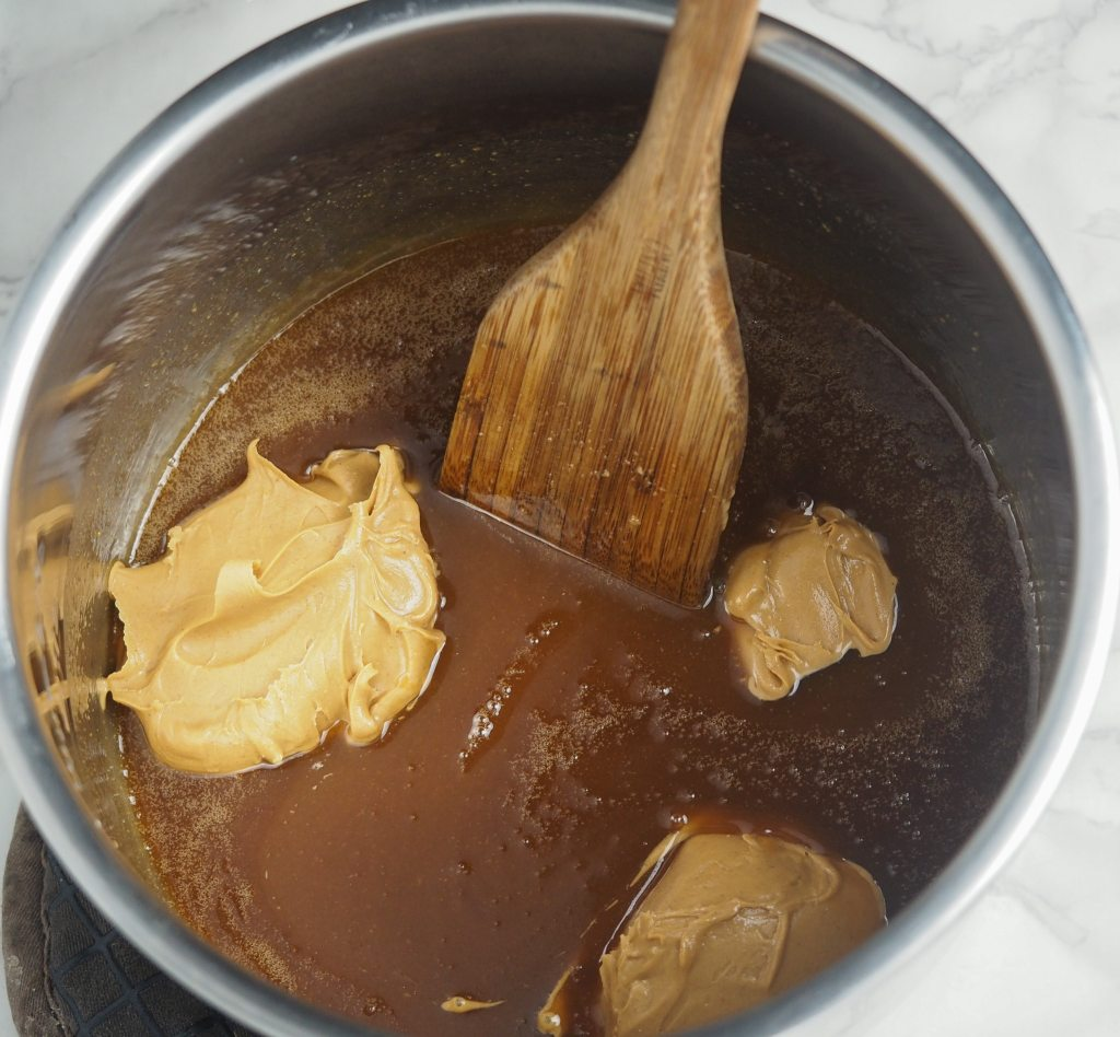 overhead view of cooked peanut butter fudge in the instant pot liner with peanut butter and wooden spatula